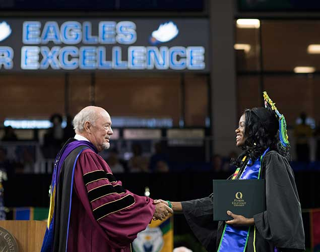 Photo of President Martin shaking hands with graduating student